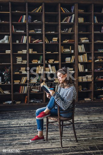 istock Young woman reading in the library 691832150