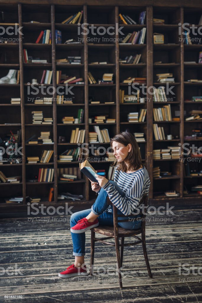 Young woman reading in the library stock photo