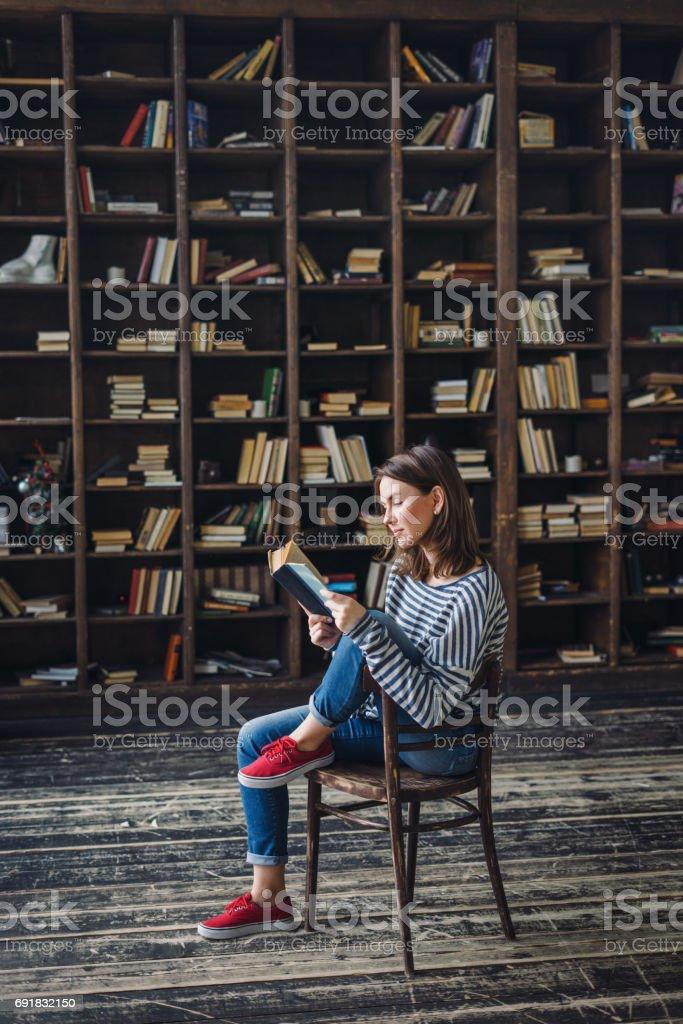 Junge Frau, die Lesung in der Bibliothek – Foto