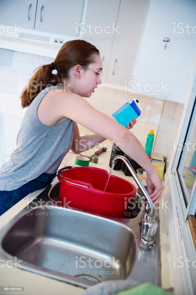 Young woman reading instructions of cleaning products. stock photo