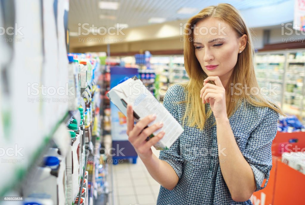Young woman reading label milk Young woman reading label milk Adult Stock Photo
