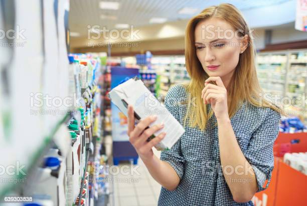 Young Woman Reading Label Milk Stock Photo - Download Image Now