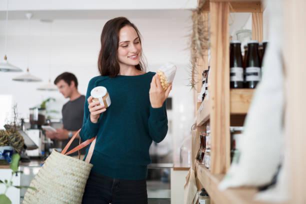 Junge Frau liest Etikett auf Produkten im Laden – Foto
