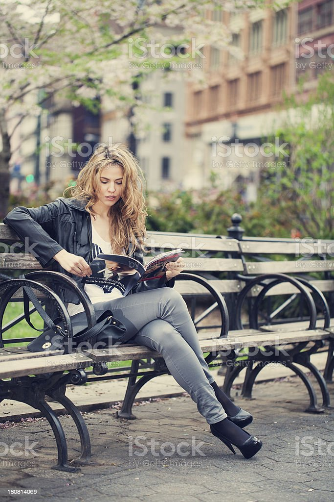Young woman reading magazine in city park royalty-free stock photo