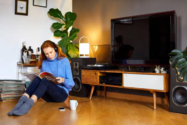 Junge Frau beim hören von Musik Magazin lesen – Foto
