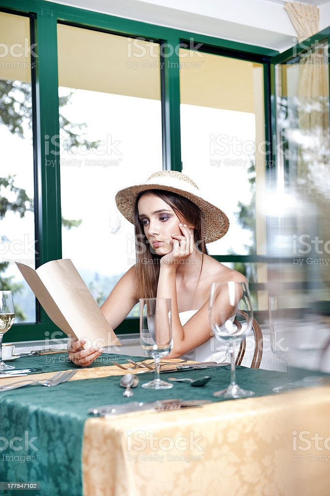 Young woman reading menu in restaurant stock photo