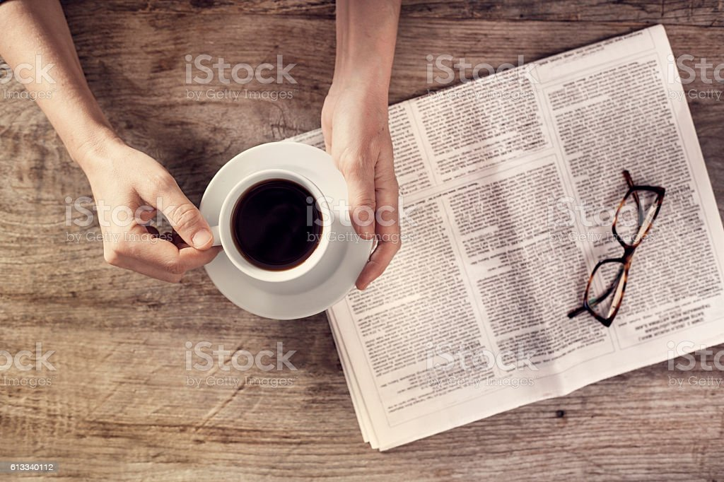 Young woman reading newspaper and holding coffee cup stock photo