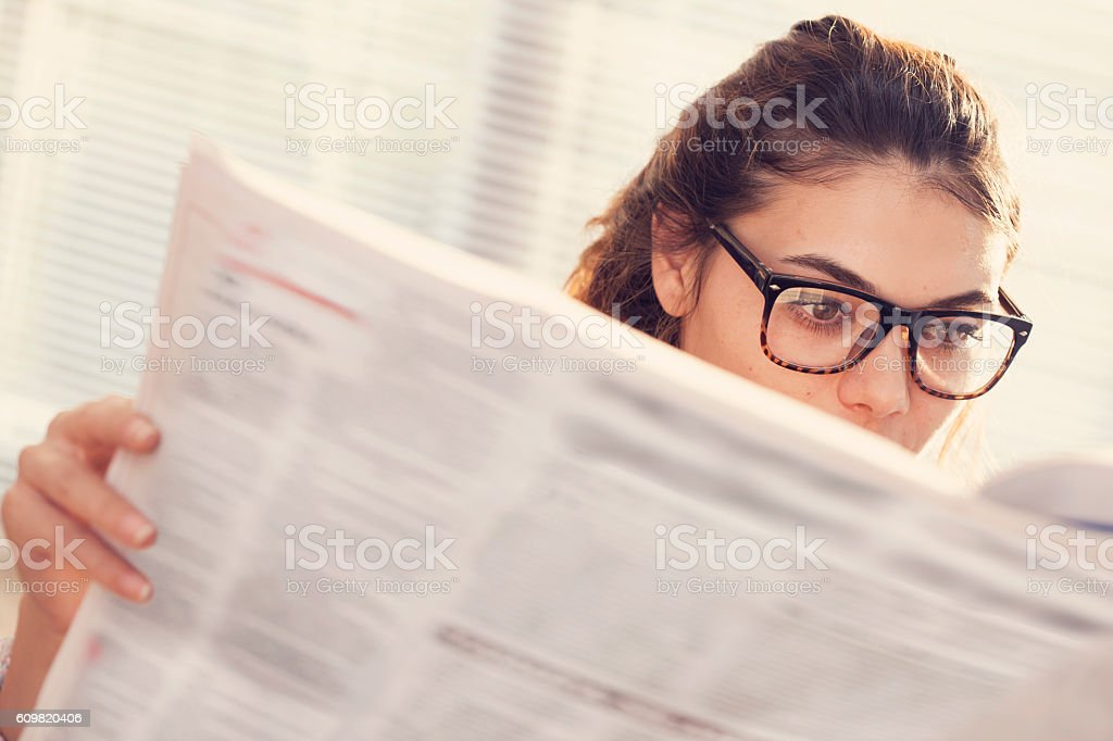 Young woman reading newspaper stock photo