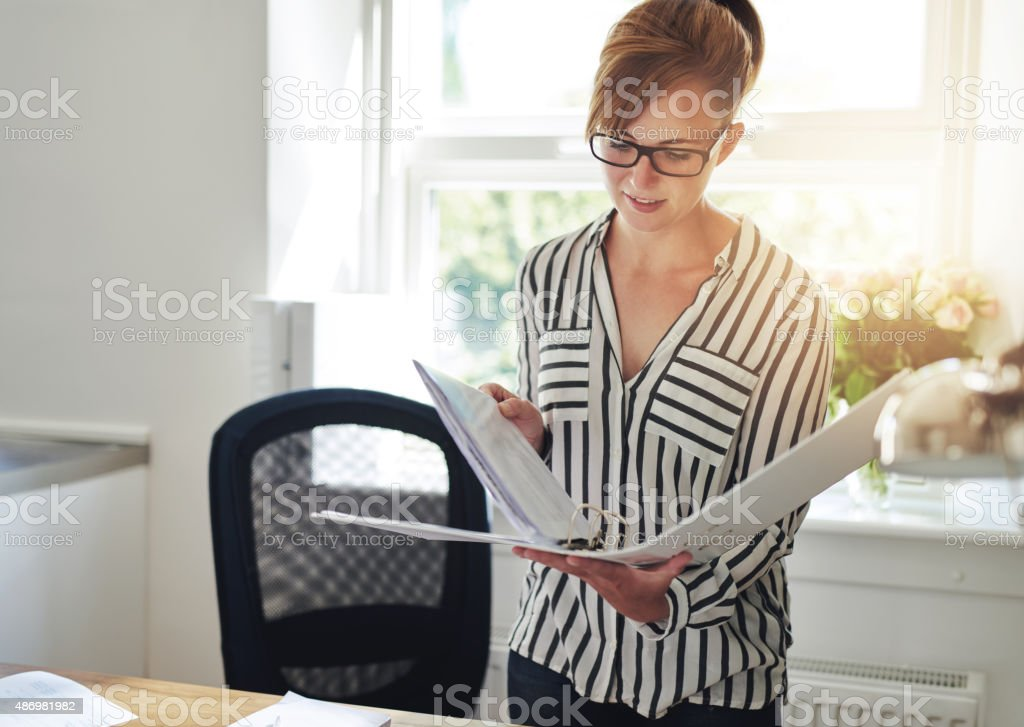 Young woman reading notes in an office binder stock photo