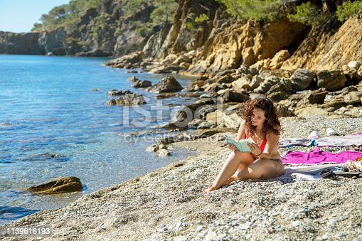 Beautiful young woman reading novel at beach on sunny day. Full length of female is relaxing on shore. She is spending summer vacation.