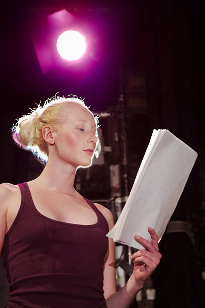 young woman reading script on stage - audition stock photos and pictures