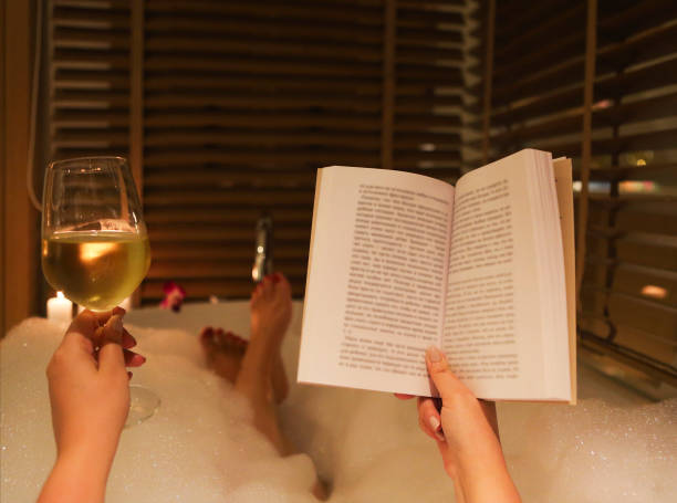 Young woman reading the book and drinking white wine in bath with foam and candles stock photo