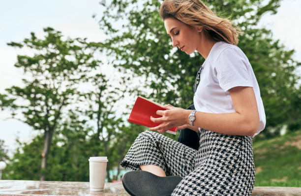 Young woman reading the book with disposable cup of coffee in the park. Pretty female relaxing with takeaway coffee cup in the hand. Student girl drinking coffee and learning outside. stock photo