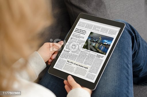 A digital newspaper on a modern tablet computer held by a young woman who is reading the day's news. The newspaper was created by myself in Indesign, I own the copy right of the design and layout. The image of Frankfurt on the digital device is my own, I own the copy right. The text is all lorem ipsum except for the titles, which are generic and entirely fictional – these were written by myself.