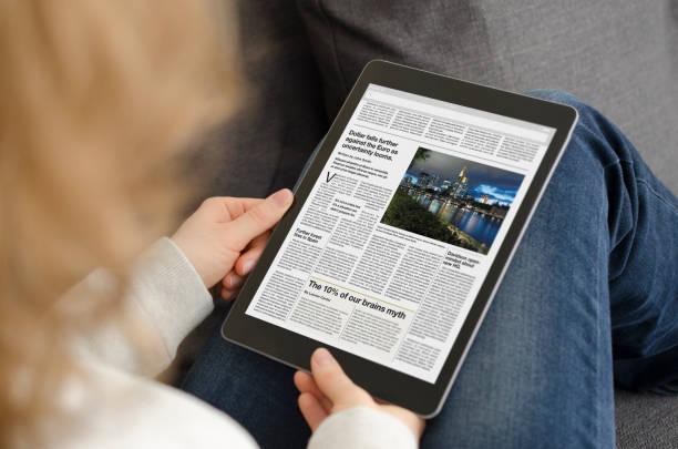 jonge vrouw lezen van het nieuwsartikel op een moderne tablet-computer - woman home magazine stockfoto's en -beelden