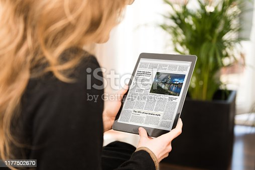 A digital newspaper on a modern tablet computer held by a young woman, who is reading the day's news. The newspaper on the device screen was created by myself in Indesign, I own the copy right of the design and layout. The image of Frankfurt on the device is my own. I own the copy right. The text is all lorem ipsum except for the titles, which are fictional – these were written by myself.