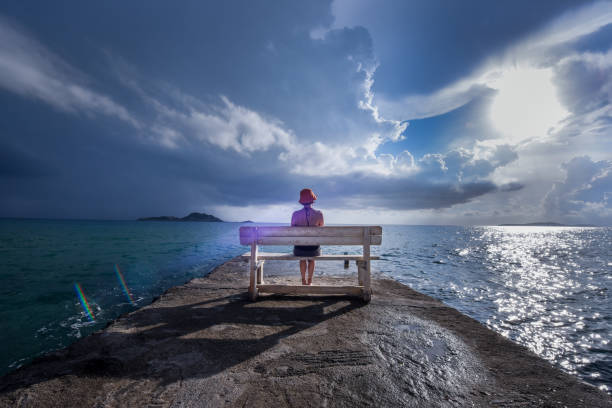 young woman reads a book on a bench at a harbor near the sea with dramatic sky in the backgroung - storm stock photos and pictures