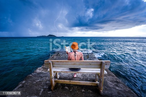 Dramatic  summer moment caught on a camera. Young woman is reading a book on a bench at a pear near the sea, while storm is approaching. Dramatic sky in the background with caught lightning