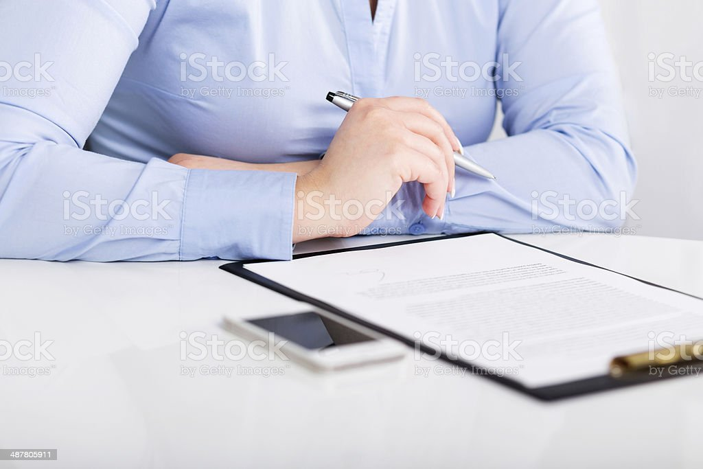 Young woman reads a signed contract stock photo