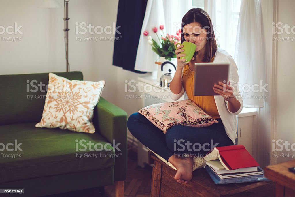 Young woman reads a tablet and drinks coffee at home stock photo