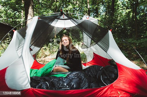 Young woman backpacker with long hair reading interesting book during bright summer sunrise sitting in the red tent hidden in the beautiful forest in Ukraine