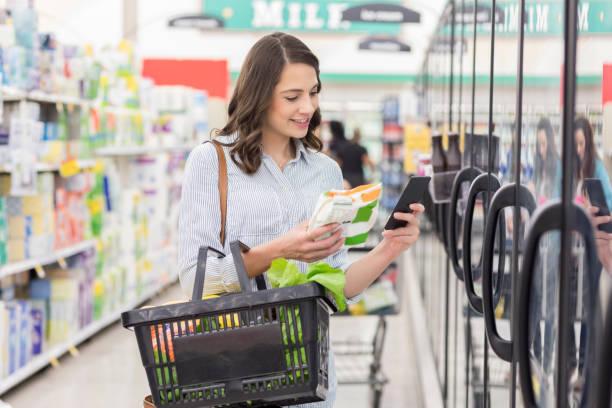 젊은 여 자가 읽는 냉동 식품 제품에 - 냉동식품 뉴스 사진 이미지