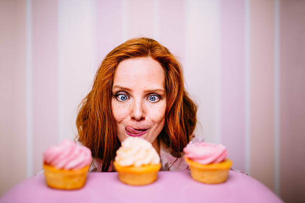 young woman really wants to eat cupcakes - passie stockfoto's en -beelden