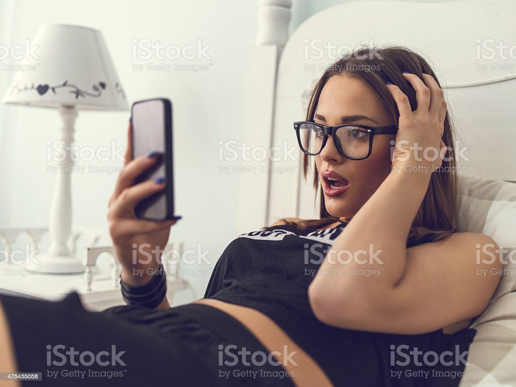 Young woman received a shocking text message on mobile phone. stock photo