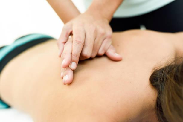 junge frau erhält eine rückenmassage in ein spa-center. - chiropraktik wellness stock-fotos und bilder