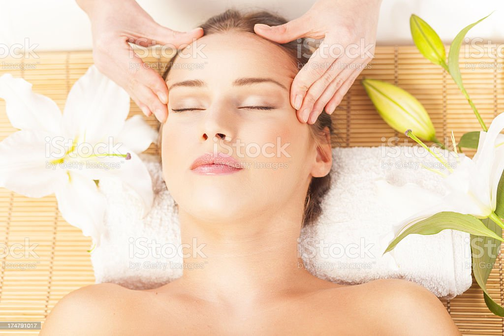 Young woman receiving a head massage in a beauty salon royalty-free stock photo