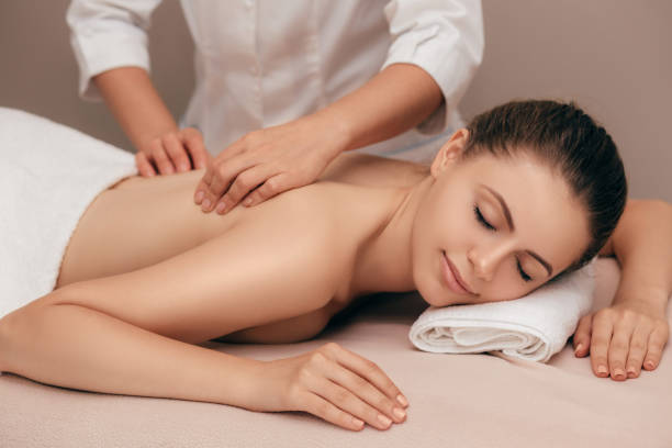 young woman receiving a massage at spa salon - massaggio foto e immagini stock