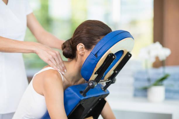 young woman receiving back massage - krzesło zdjęcia i obrazy z banku zdjęć