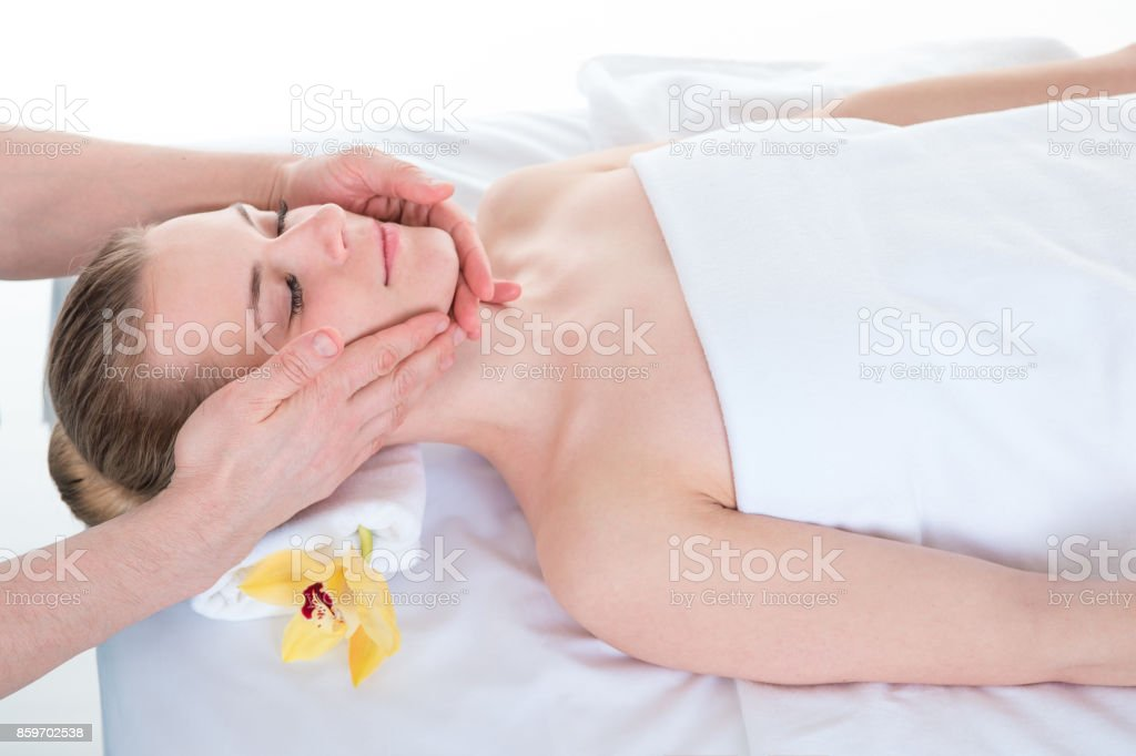Young woman receiving head massage by masseur at health spa stock photo