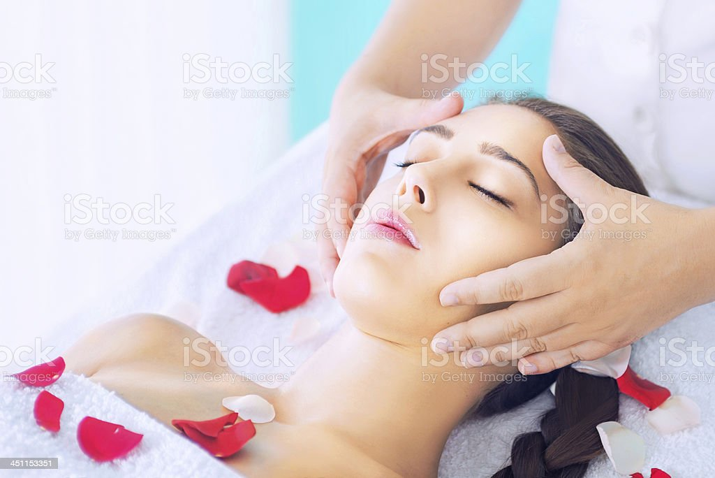 Young woman receiving head massage stock photo
