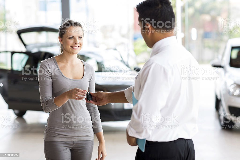 young woman receiving her new car key stock photo