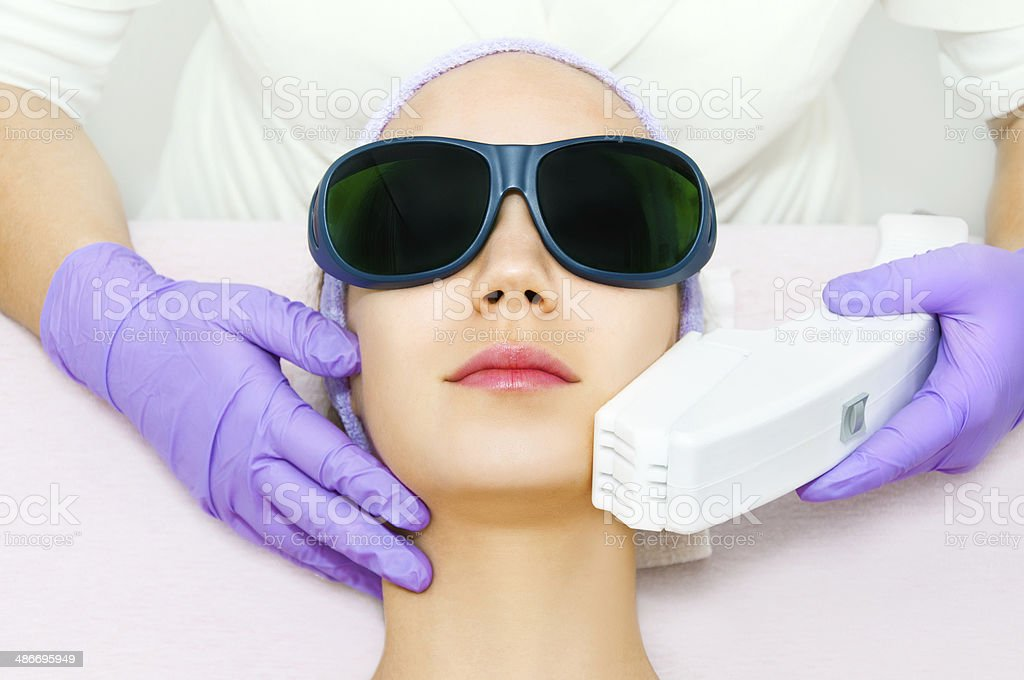 Young woman receiving laser epilation stock photo