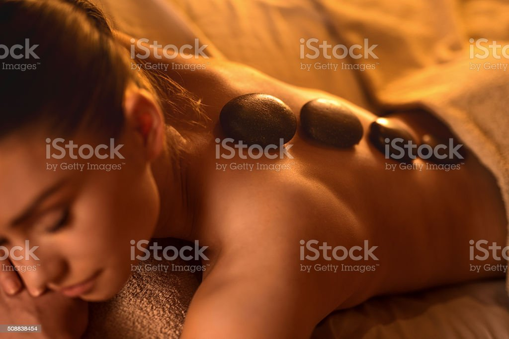 Young woman receiving lastone therapy at spa. stock photo
