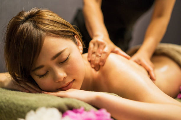 young woman receiving oil massage - spa treatment stock photos and pictures