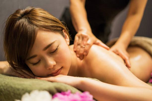 Jeune femme recevant l'huile de massage - Photo