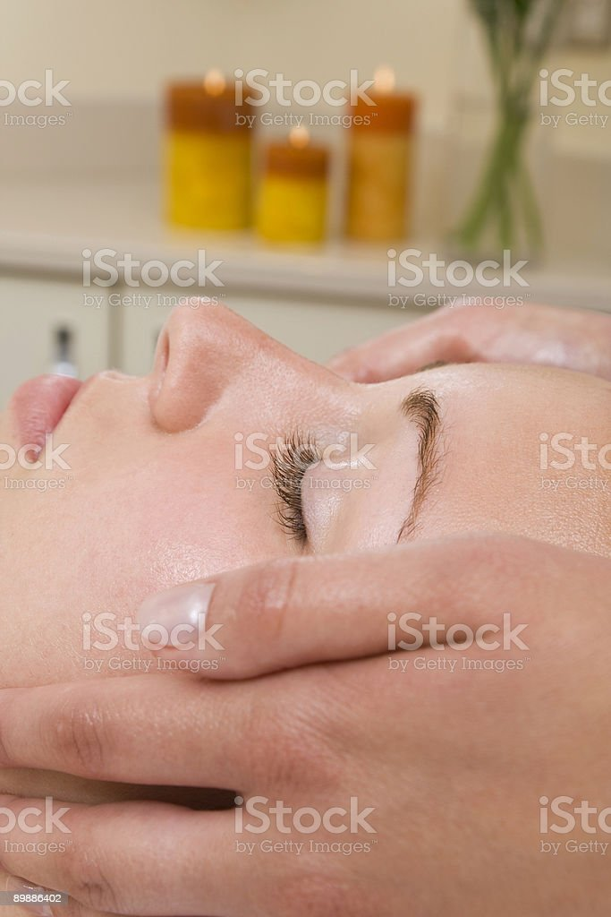 Young Woman Receiving Relaxing Facial Treatment At Health Spa royalty-free stock photo
