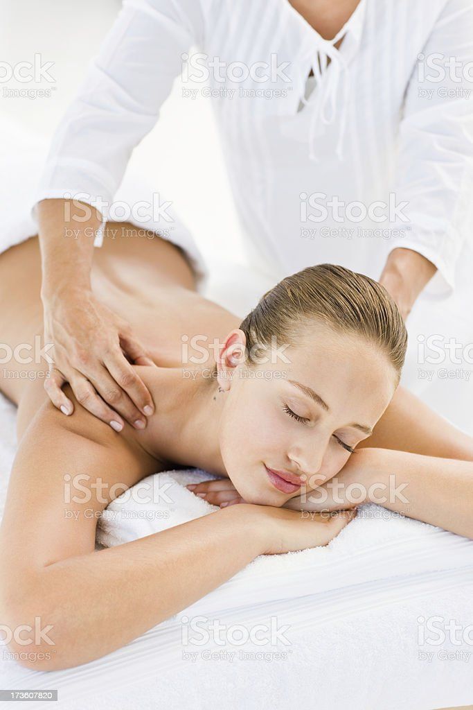 Young woman receiving shoulder massage at spa royalty-free stock photo