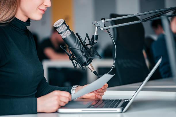 jonge vrouw het opnemen van een podcast in een studio, close-up. - podcast stockfoto's en -beelden
