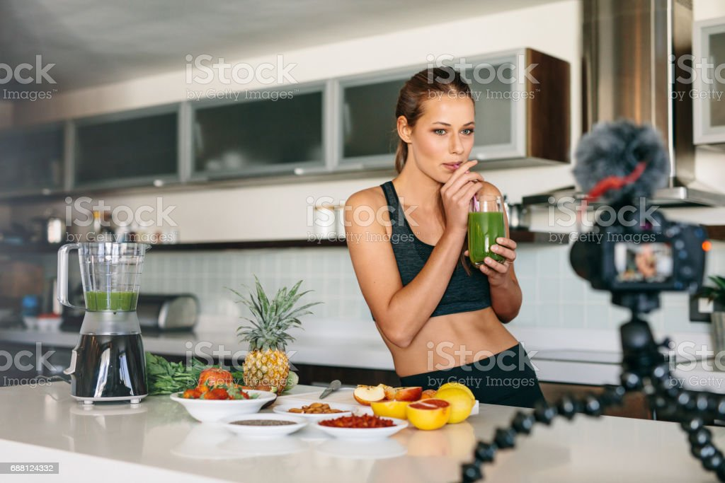Young woman recording content for her video blog in kitchen. stock photo