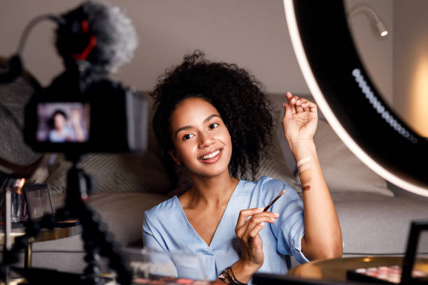young woman recording video for her online course. makeup artist with palette of tonal creams on hand. - side hustle stock pictures, royalty-free photos & images