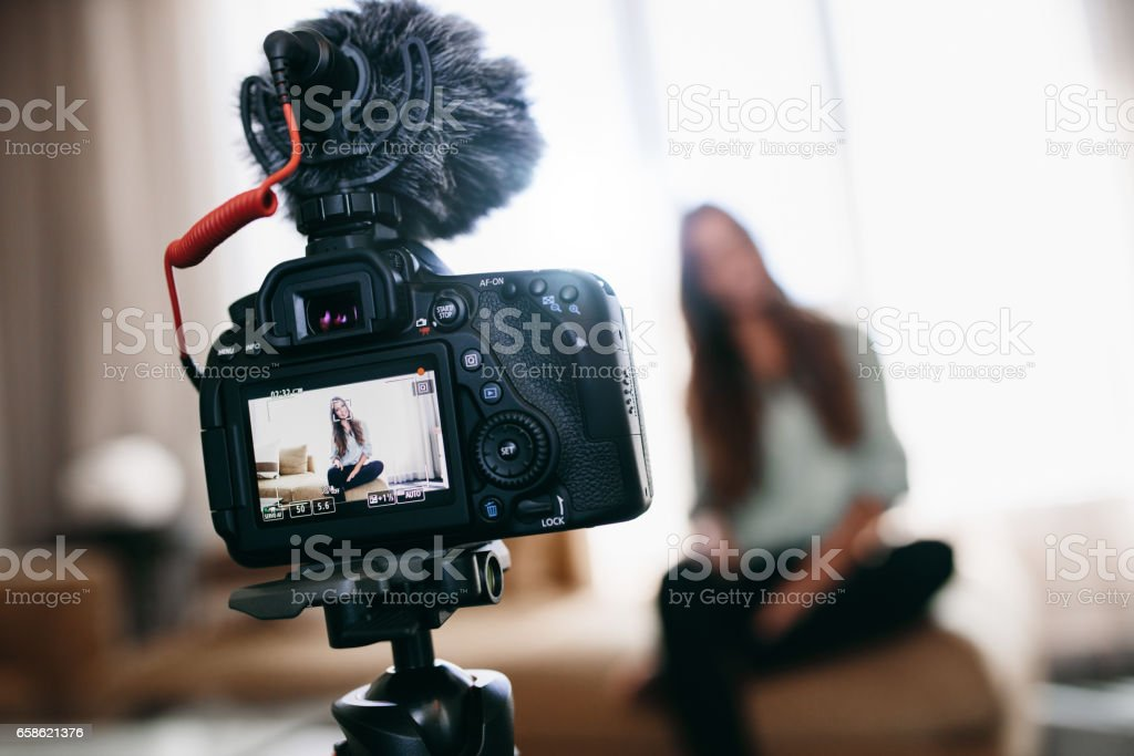 Young woman recording video for her vlog using camera with microphone mounted on tripod. stock photo