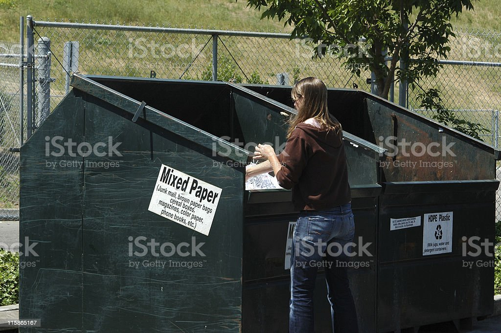 young woman recycling mixed paper at recycling center royalty-free stock photo