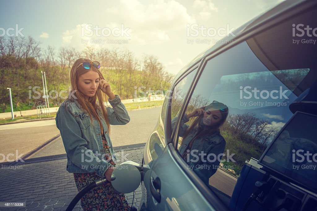 Young woman refilling car with fuel stock photo