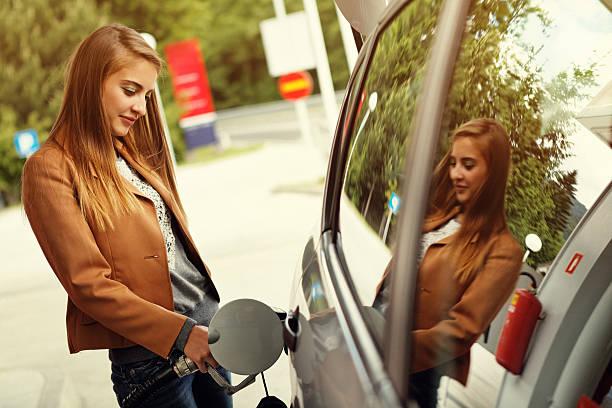 joven mujer puede rellenarse con gas coche bomba - echar combustible fotografías e imágenes de stock