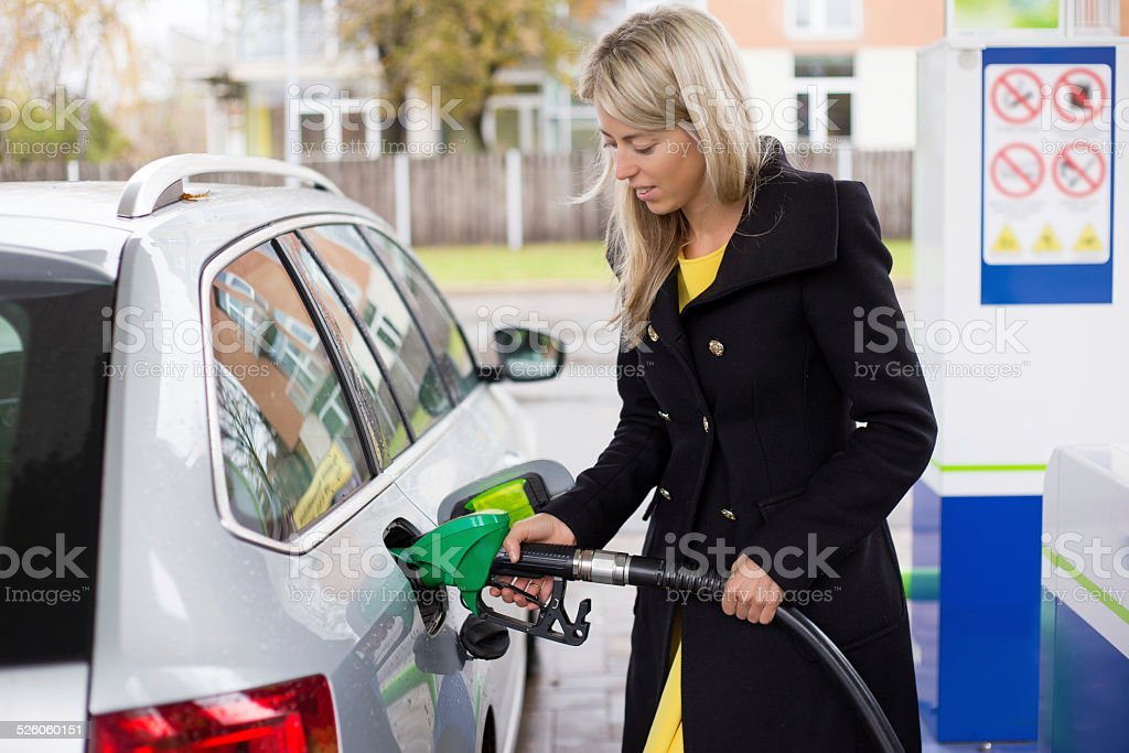 Young woman refilling petrol in gas station stock photo