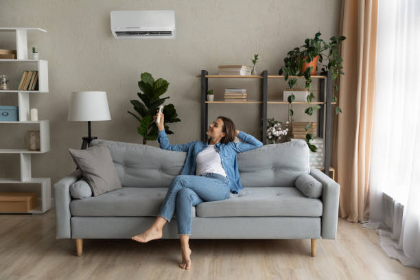Young woman relax on couch turn on AC stock photo